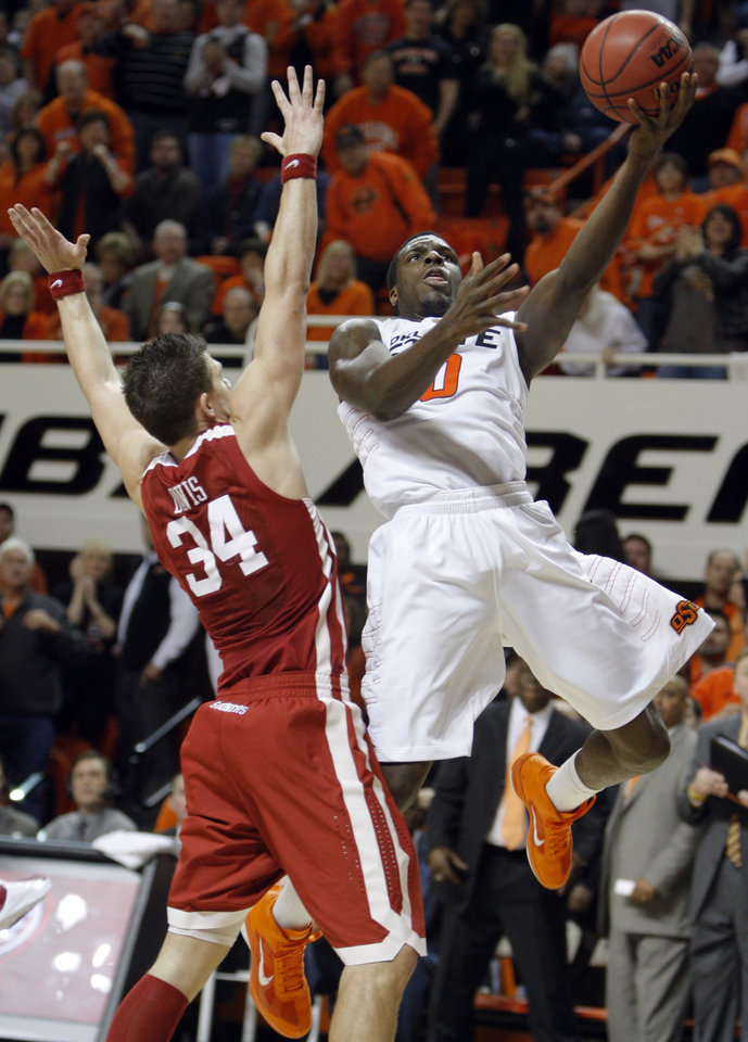 Photo - Oklahoma State's Jean-Paul Olukemi (0) shoots over Oklahoma's Cade Davis (34) during the Bedlam men's college basketball game between the University of Oklahoma Sooners and Oklahoma State University Cowboys at Gallagher-Iba Arena in Stillwater, Okla., Saturday, February, 5, 2011. Photo by Sarah Phipps, The Oklahoman