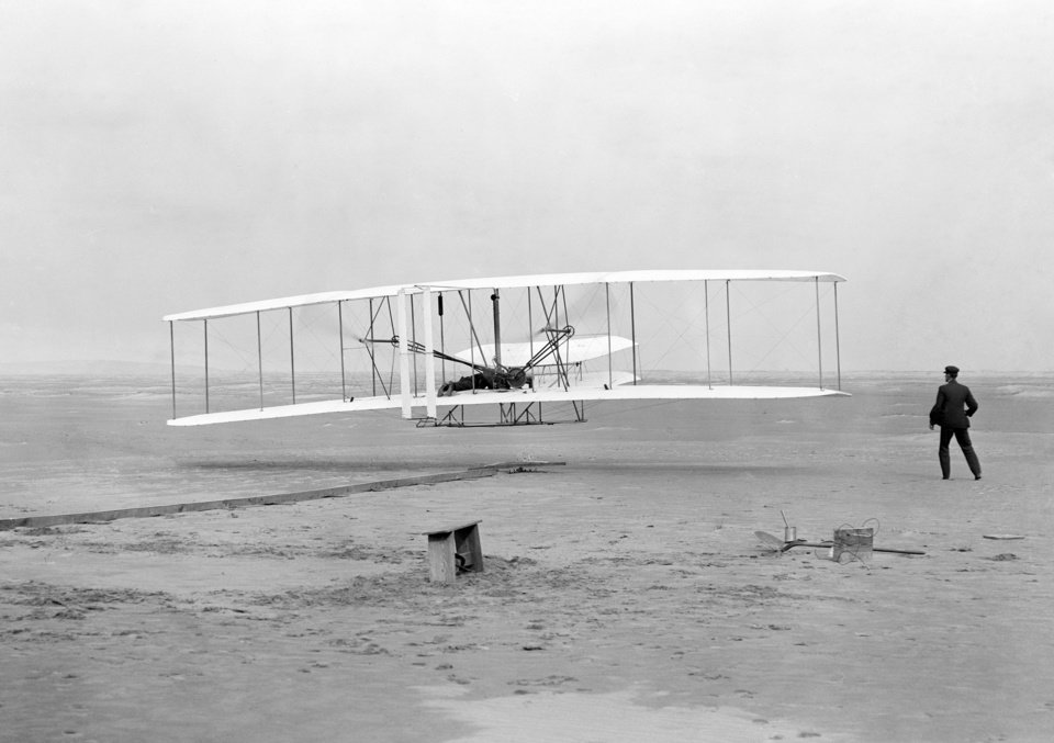 Photo -  Orville Wright, lying at the controls on the lower wing, pilots the Wright Flyer on the first powered flight by a heavier-than-air aircraft, Dec. 17, 1903, at Kitty Hawk, N.C. In the moments before going airborne, his brother, Wilbur Wright, watching right, guided and steadied the plane as it accelerated along the starting rail at left. (AP Photo/Library of Congress, John T. Daniels)