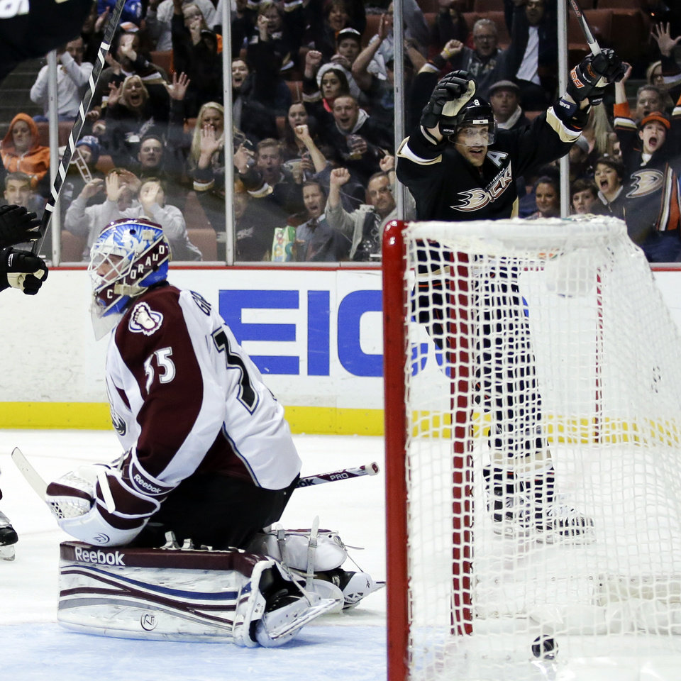 Photo - Anaheim Ducks right wing Teemu Selanne, right, celebrates his goal past Colorado Avalanche goalie Jean-Sebastien Giguere during the second period of an NHL hockey game in Anaheim, Calif., Sunday, Feb. 24, 2013. (AP Photo/Chris Carlson)