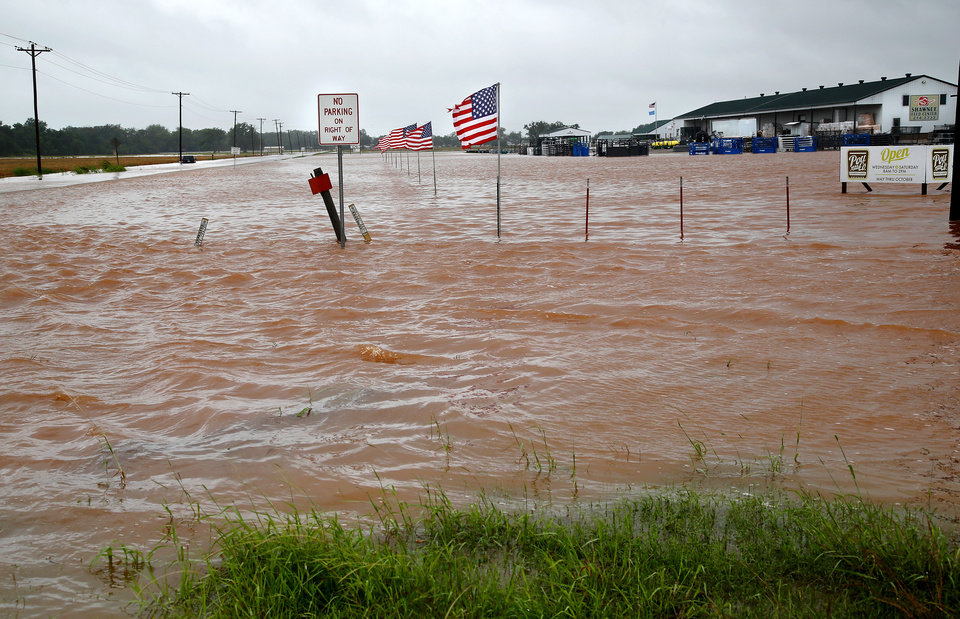 Photo - Rain from Hurricane Bill produced localized flooding in areas of Pottawatomie County on Thursday, June 18,  2015.   Hardesty Road and US 177. This photo shows a flooded field and parking lot west of US 177 in Shawnee. In background is Shawnee Feed Center. Photo by Jim Beckel, The Oklahoman.
