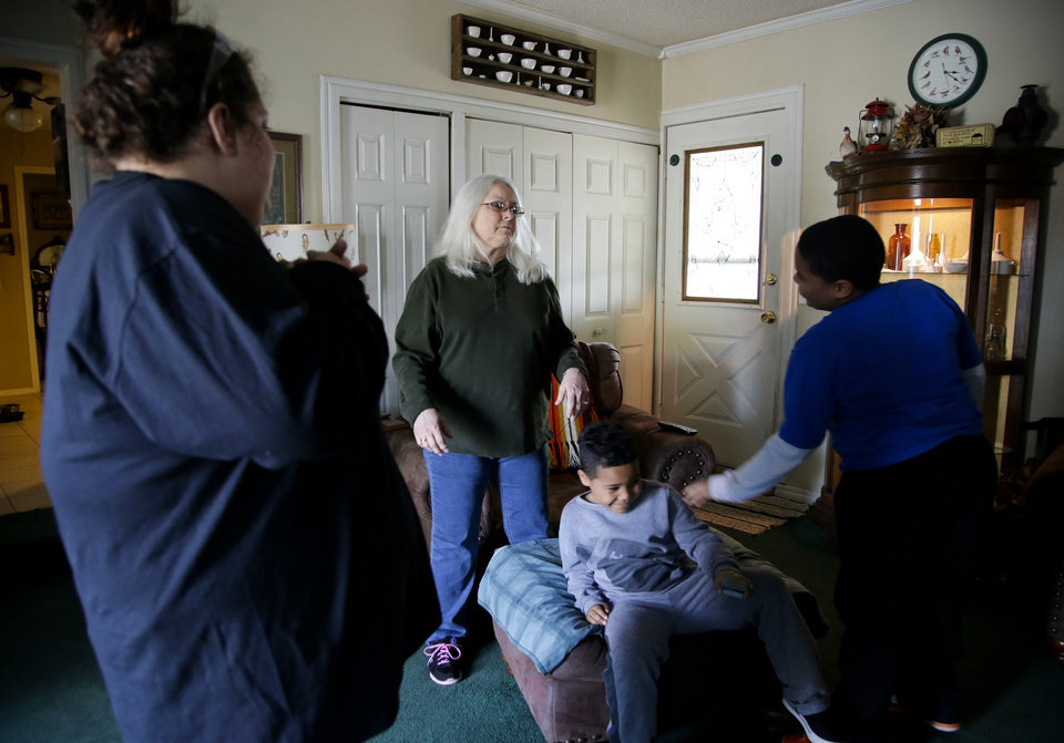 Photo -  Desha Bailey, left, talks to her grandma, Joyce Black, center, as she picks up her two sons, Isaiah and Jakobie Roberson, after her shift at Whirlpool. [Photo by Jessie Wardarski, Tulsa World]