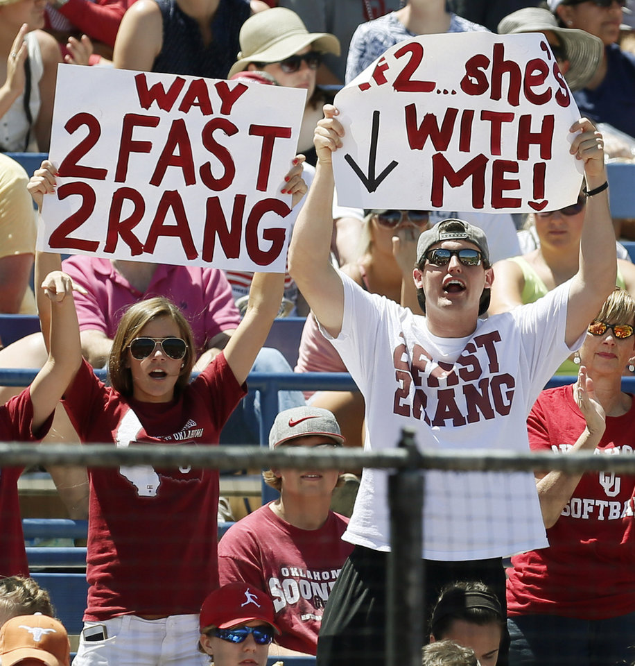 Photo - Cabria Turang, left, and Tress Way hold signs supporting OU softball player Brianna Turang (2) during an NCAA softball game in the Women's College World Series between Oklahoma and Texas at ASA Hall of Fame Stadium in Oklahoma City, Saturday, June 1, 2013. Cabria Turang is Brianna Turang's sister, and Tress Way, a former OU football player, is engaged to Brianna Turang. Oklahoma won 10-2 in five innings. Photo by Nate Billings, The Oklahoman