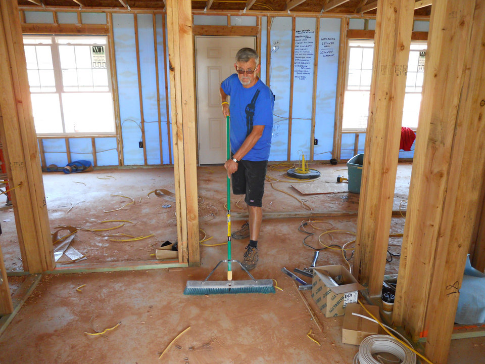 Photo - Gary Farnum sweeps up a house under construction through Central Oklahoma Habitat for Humanity. Farnum, who suffered a terrible brain disorder, volunteers twice a week.   - Provided