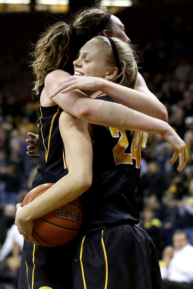 Iowa guard Jaime Printy (24) hugs center Morgan Johnson (12) during the closing seconds of their NCAA college basketball game against Iowa State, Thursday, Dec. 6, 2012, in Iowa City, Iowa. Iowa won 50-42. (AP Photo/Cedar Rapids Gazette, Brian Ray)  MAGS OUT
