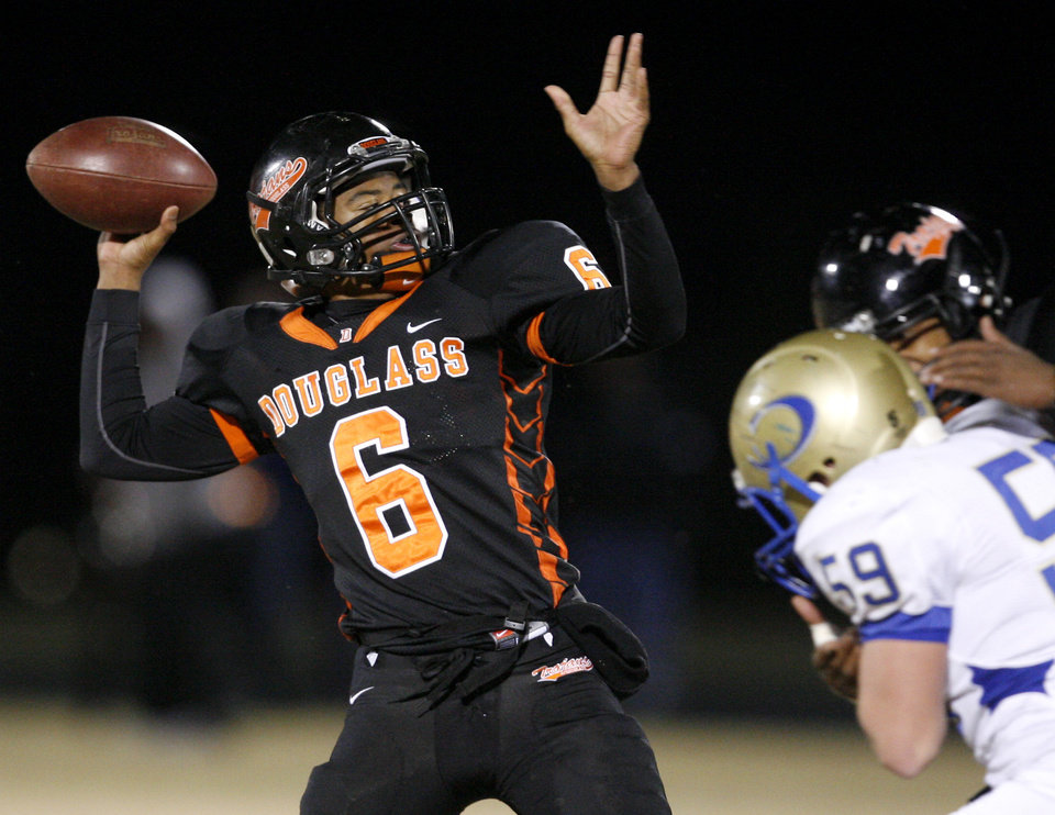 Photo - Douglass' Shon Bridges throws a touchdown pass during a high school football playoff game against Oologah in Oklahoma City, Friday, Nov. 19, 2010.  Photo by Bryan Terry, The Oklahoman