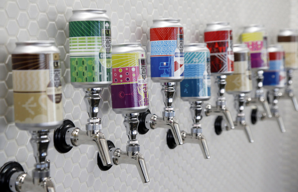 Photo -  Beer taps are adorned with beer cans at the Elk Valley Brewing Company, 1210 N Hudson Ave. [Photo by Nate Billings, The Oklahoman]