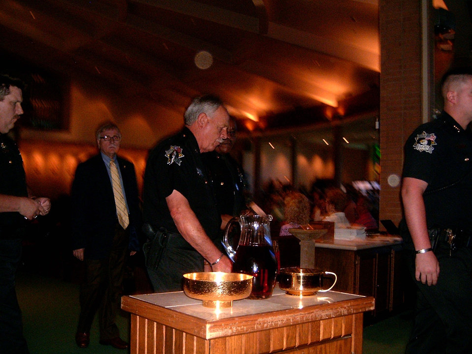 Photo - A law enforcement officer participates in the Blue Mass held recently at St. John the Baptist Catholic Church in Edmond.  STEVE GUST - STEVE GUST
