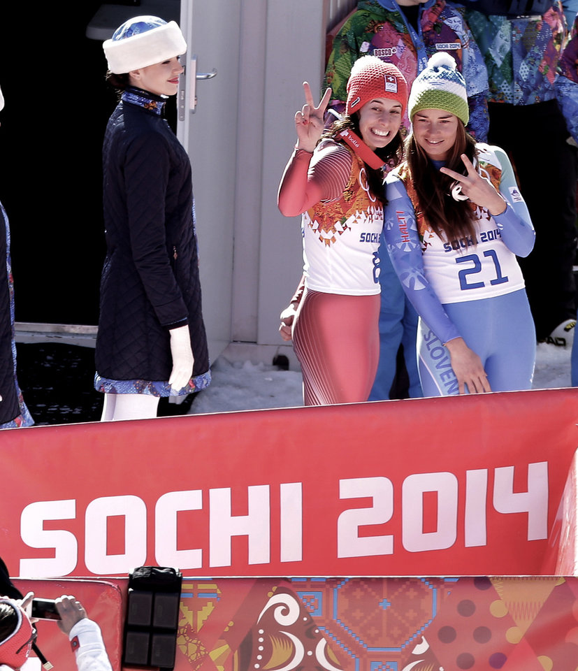 Photo - Women's downhill gold medal winners Switzerland's Dominique Gisin, left, and Slovenia's Tina Maze pose for photos before a flower ceremony at the Sochi 2014 Winter Olympics, Wednesday, Feb. 12, 2014, in Krasnaya Polyana, Russia. (AP  Photo/Charlie Riedel)