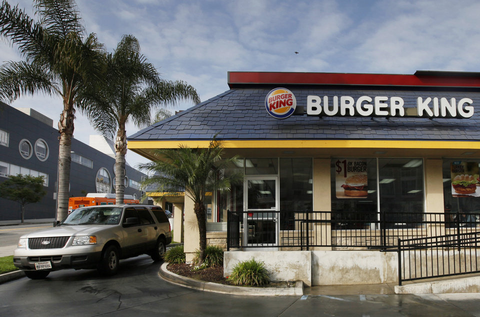 Photo - In this Thursday, April 25, 2013, photo, a car stops at the drive-thru at a Burger King restaurant near downtown Los Angeles. Burger King reports their quarterly earnings on Friday, April 26, 2013. (AP Photo/Nick Ut)