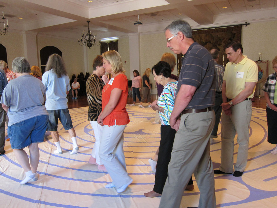 Photo - Several people walk an 11-circuit labyrinth inside St. Paul's Episcopal Cathedral, 127 NW 7, during