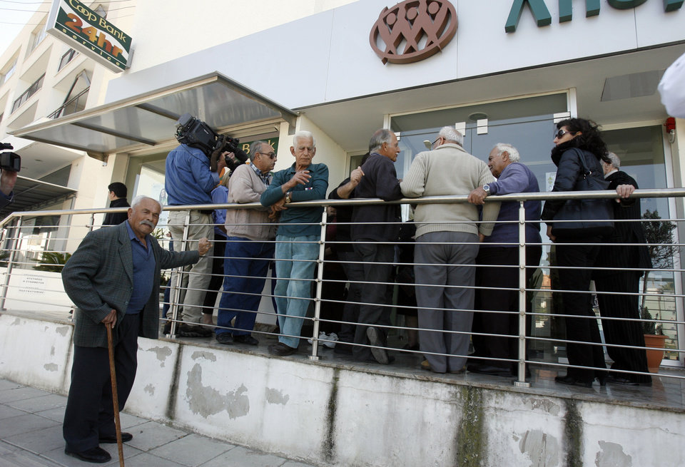 Photo - People wait outside a Coop bank branch in Nicosia, Cyprus, Thursday, March 28, 2013. Bank branches across the country were being replenished with cash, and are scheduled to open for six hours at noon (10:00 GMT). Systems were frozen pending the official noon opening. (AP Photo/Philippos Christou)