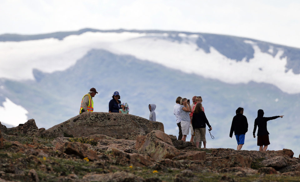 Photo - Volunteer Tundra Guardian Rick Beesley, far left, talks with visitors at a scenic overlook off Trail Ridge Road, above tree-line at Rocky Mountain National Park, west of Estes Park, Colo., Monday, July 14, 2014. Lightning killed two people last weekend just miles apart in the popular park, where summer storms can close in quickly with deadly results. (AP Photo/Brennan Linsley)