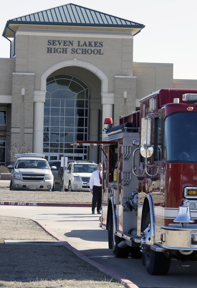 Photo - A fire truck is parked outside Seven Lakes High School Monday, Jan. 13, 2014, in Katy, Texas after bomb squad was called to the school after a potentially explosive device was found. Students were evacuated and then released for the day. (AP Photo/Pat Sullivan)