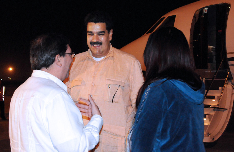 Photo - In this photo provided by Cuba's state newspaper Granma, Cuban Foreign Minister Bruno Rodriguez , left, talks with Venezuela's Vice President Nicolas Maduro, center, as Venezuelan Attorney General Cilia Flores watches at the Jose Marti International Airport in Havana on Saturday, Dec. 29, 2012. Maduro arrived in Cuba to visit Venezuelan President Hugo Chavez, who is recovering from a surgery_ his fourth operation related to his pelvic cancer since June 2011. (AP Photo/Granma, Juvenal Balan Neyra )