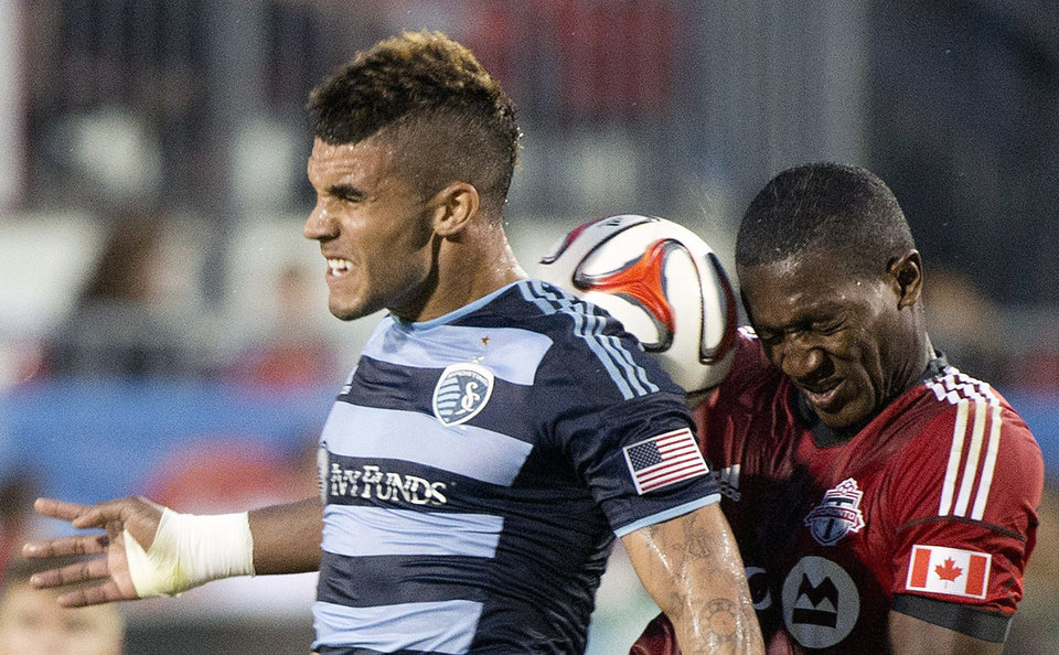 Photo - Sporting Kansas City forward Dom Dwyer, left, heads the ball past Toronto FC defender Doneil Henry, right, during second-half MLS soccer game action in Toronto, Saturday, July 26, 2014. (AP Photo/The Canadian Press, Nathan Denette)