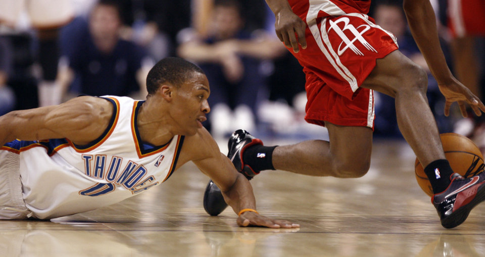 Oklahoma City's Russell Westbrook (0) dives for a loose ball by Houston's Aaron Brooks during the NBA basketball game between the Oklahoma City Thunder and the Houston Rockets, Wednesday, March 24, 2010,  at the Ford Center in Oklahoma City. Photo by Sarah Phipps, The Oklahoman  ORG XMIT: KOD