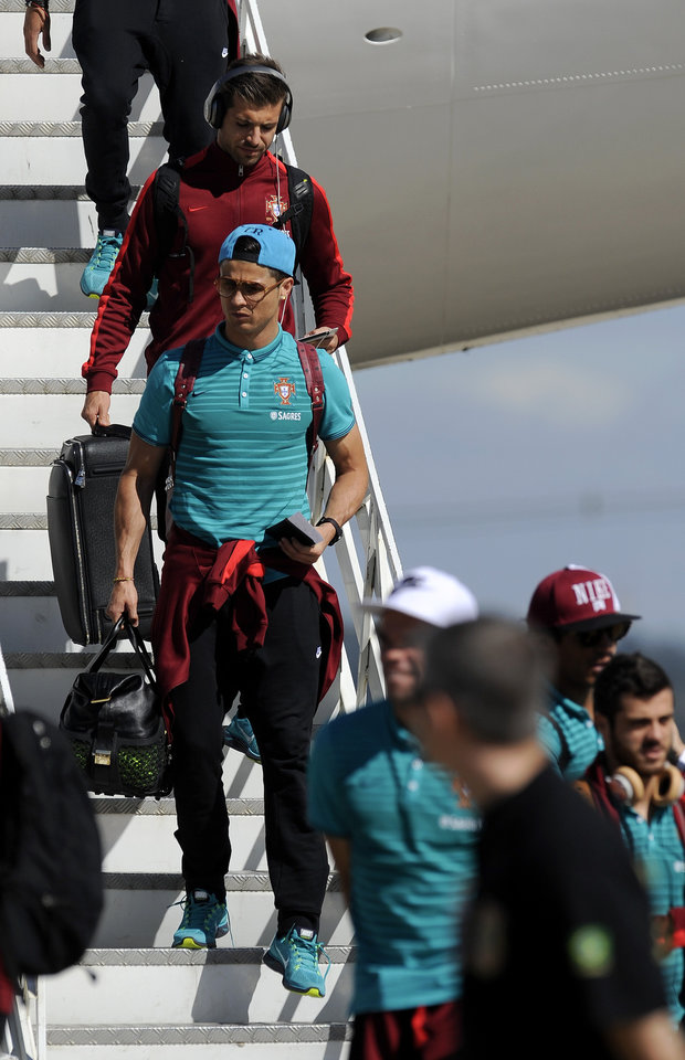 Photo - Portugal's soccer player Cristiano Ronaldo, front left, walks down from a plane as they arrive at the Viracopos airport, in Campinas, Brazil, Tuesday, June 11, 2014. Portugal will play in group G of Brazil's 2014 soccer World Cup. (AP Photo/Paulo Duarte)
