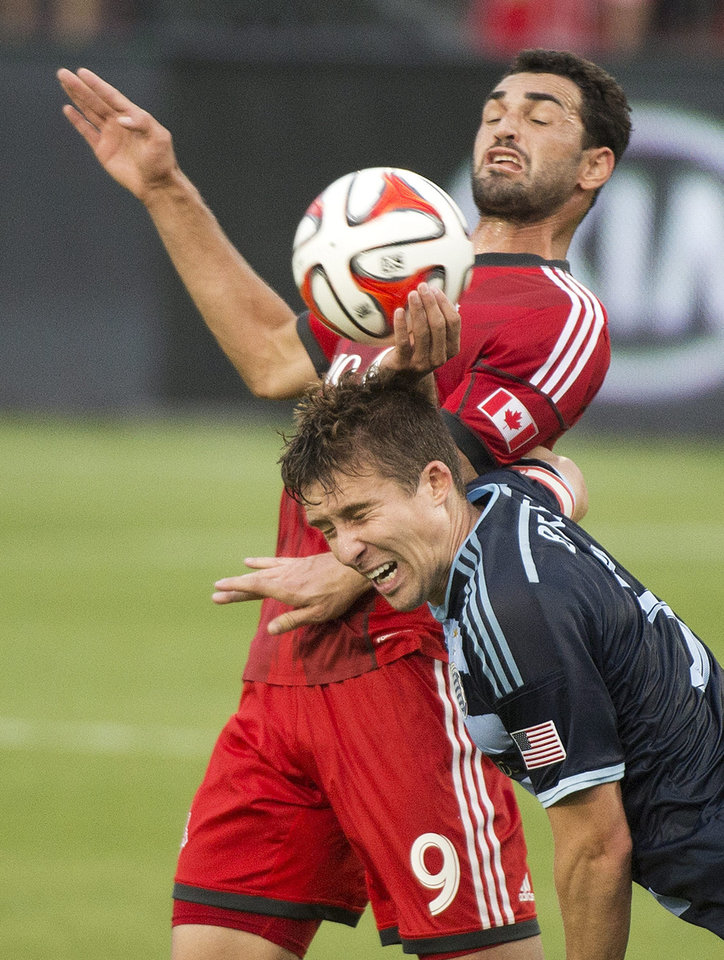 Photo - Toronto FC defender Doneil Henry, rear, competes for the ball against Sporting Kansas City forward C.J. Sapong during the first half of an MLS soccer game Saturday, July 26, 2014, in Toronto. (AP Photo/The Canadian Press, Nathan Denette)