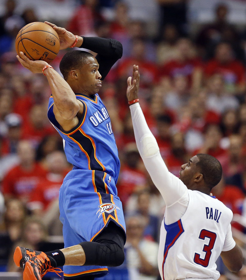 Photo - Oklahoma City's Russell Westbrook (0) passes away from Los Angeles' Chris Paul (3) during Game 6 of the Western Conference semifinals in the NBA playoffs between the Oklahoma City Thunder and the Los Angeles Clippers at the Staples Center in Los Angeles, Thursday, May 15, 2014. Photo by Nate Billings, The Oklahoman