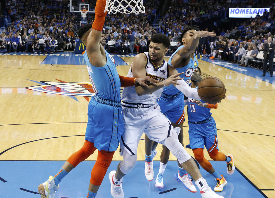 Photo - Denver Nuggets guard Jamal Murray, center, looks to pass around Oklahoma City Thunder guard Russell Westbrook, left, and guard Terrance Ferguson, right, during the second half of an NBA basketball game Friday, March 29, 2019, in Oklahoma City. (AP Photo/Sue Ogrocki)