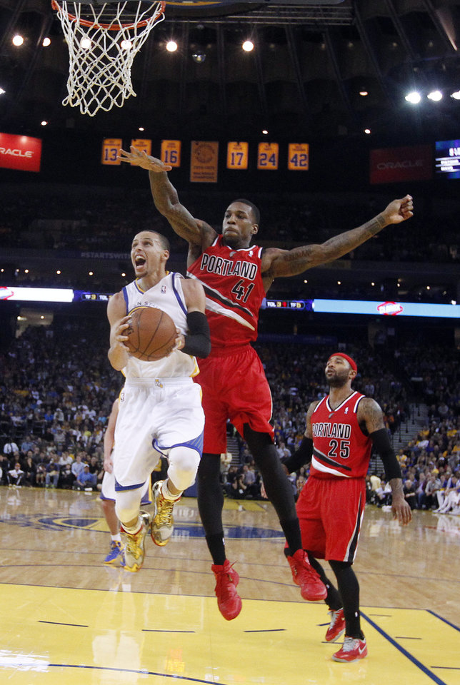 Photo - Golden State Warriors' Stephen Curry, left, drives to the basket past Portland Trail Blazers' Thomas Robinson (41) and Mo Williams (25) during the second half of an NBA basketball game on Sunday, Jan. 26, 2014, in Oakland, Calif. Golden State won 103-88. (AP Photo/Marcio Jose Sanchez)