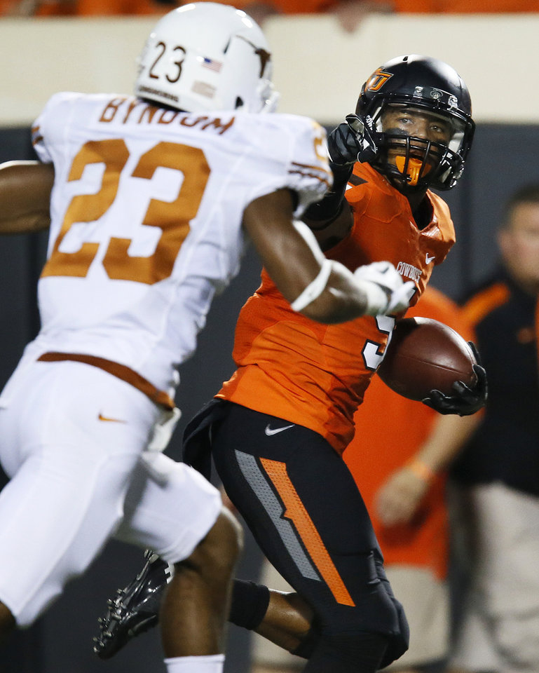Photo - OSU's Josh Stewart (5) takes a catch for a touchdown past UT's Carrington Byndom (23) in the first quarter during a college football game between Oklahoma State University (OSU) and the University of Texas (UT) at Boone Pickens Stadium in Stillwater, Okla., Saturday, Sept. 29, 2012. Photo by Nate Billings, The Oklahoman