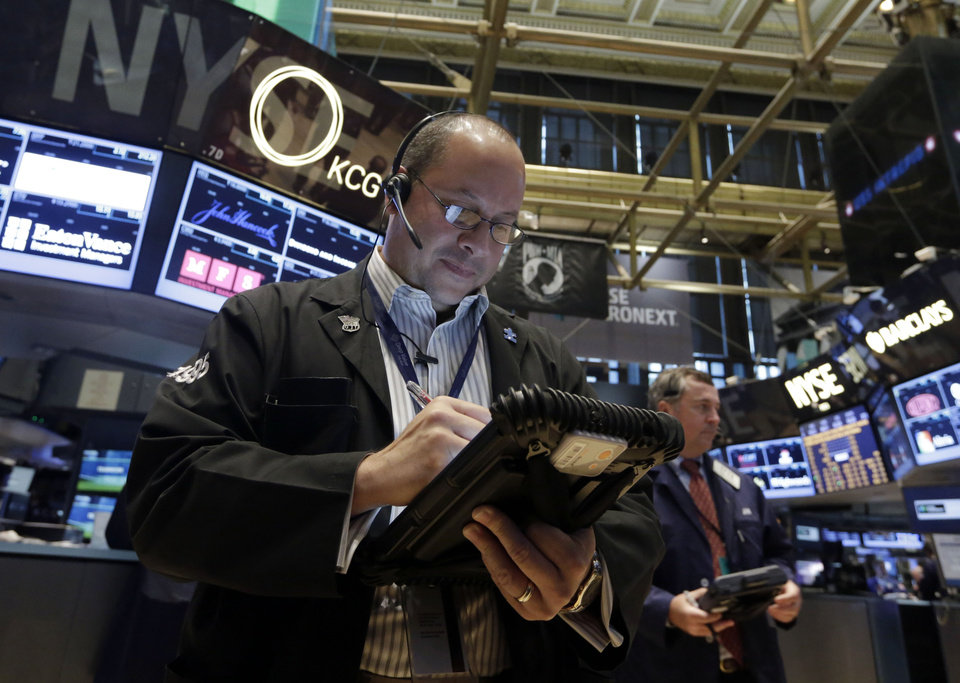 Photo - Trader Jeffrey Vasquez works on the floor of the New York Stock Exchange Friday, Aug. 16, 2013. Stocks bounced back Friday from consecutive days of significant declines, with more evidence of a rebounding U.S. housing market.(AP Photo/Richard Drew)