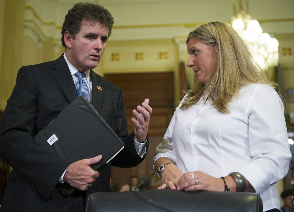 Photo - Rep. Mike Fitzpatrick, R-Pa., talks with witness Kristen Ruell, authorization quality review specialist in the Pension Management Center at the Veterans Affairs Philadelphia Regional Office, prior to her testifying to the House Committee on Veterans Affairs hearing to review the Veterans Benefits Administrations progress in achieving VA's goal of ending its disability compensation claims backlog by 2015, on Capitol Hill in Washington, Monday, July 14, 2014. (AP Photo/Cliff Owen)