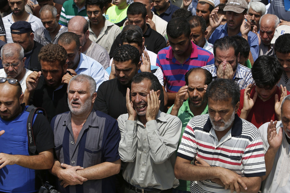 Photo - A relative bursts into tears as mourners pray in front of the bodies of seven members of the Kelani family, killed overnight by an Israeli strike in Gaza City, during their funeral in Beit Lahiya, northern Gaza Strip, on Tuesday, July 22, 2014. Ibrahim Kelani, 53, his wife Taghreed and their five children, were killed in the strike on a Gaza City highrise. Ibrahim's brother Saleh Kelani said Tuesday that his brother and his brother's children, ranging in age from four to 12, had German citizenship, while his wife had not. The family had rented the apartment in the high-rise after fleeing their home in the northern Gaza town of Beit Lahiya which came under heavy shelling by the Israeli army. (AP Photo/Lefteris Pitarakis)