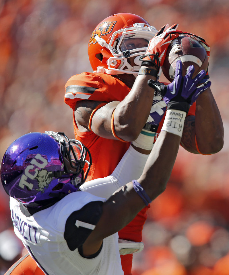 Oklahoma State's Josh Stewart (5) makes a catch over TCU's Chris Hackett (1) during a college football game between the Oklahoma State University Cowboys (OSU) and the Texas Christian University Horned Frogs (TCU) at Boone Pickens Stadium in Stillwater, Okla., Saturday, Oct. 19, 2013. Photo by Chris Landsberger, The Oklahoman