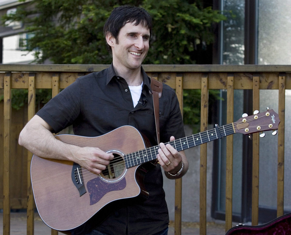 "FILE - In this July 9, 2009 file photo, Musician Dave Carroll, of the pop-folk band Sons Of Maxwell, holds his repaired Taylor guitar in Halifax, Nova Scotia. Carroll became an Internet sensation after posting a revenge song about airline customer service on YouTube with his song ""United Breaks Guitars."" Federal regulators are striking a sour note with musicians and their congressional supporters. Two years ago Congress directed the Transportation Department to write rules requiring airlines to accommodate musicians traveling with their instruments by storing the instruments in closets and overhead bins where they fit. Musicians have long complained that airlines damage or lose instruments, or force travelers to check them as baggage. The rules are due Feb. 14, 2014,, but transportation officials haven't started work on them.  (AP Photo/The Canadian Press, Andrew Vaughan)"