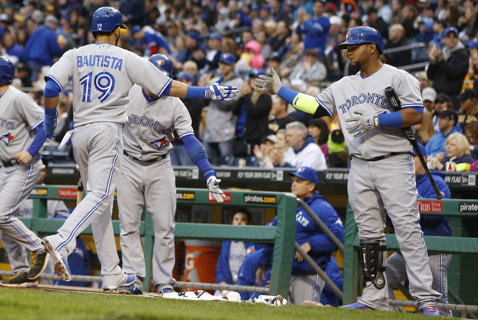 Photo - Toronto Blue Jays' Jose Bautista (19) is greeted by on deck batter Edwin Encarnacion after he scored in the first inning of the baseball game against the Pittsburgh Pirates on Friday, May 2, 2014, in Pittsburgh. (AP Photo/Keith Srakocic)
