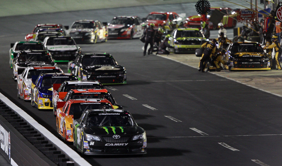 Photo - Kyle Busch (54) leads JJ Yeley (42) down pit road during a caution period in the NASCAR Nationwide series auto race at Bristol Motor Speedway on Friday, Aug. 22, 2014, in Bristol, Tenn. (AP Photo/Wade Payne)