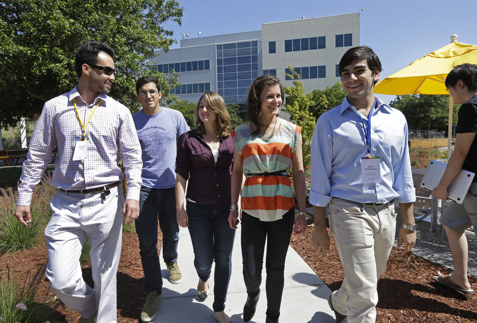 Photo - Google interns, from left, Steve Weddler, Alfredo Salinas, Lizzy Burl, Rita DeRaedt, and Alex Rodrigues walk on the Google campus, Wednesday, May 21, 2014, in Mountain View, Calif. With summer's arrival comes an influx of thousands of Silicon Valley interns, and these kids aren't just fetching coffee.  Well paid and perked, young up-and-comers from around the world who successfully navigate the competitive application process are assigned big time responsibility at firms like Google, Facebook, Drop Box and Twitter, where executives hope that a fun and stimulating summer will motivate them to come back after graduation to launch careers. (AP Photo/Ben Margot)