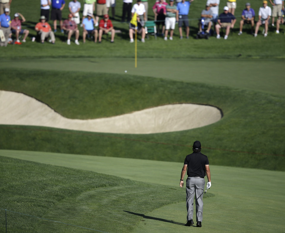 Photo - Phil Mickelson tries to take a look at his shot to the 11th green during the second round of the Memorial golf tournament Friday, May 30, 2014, in Dublin, Ohio. (AP Photo/Darron Cummings)