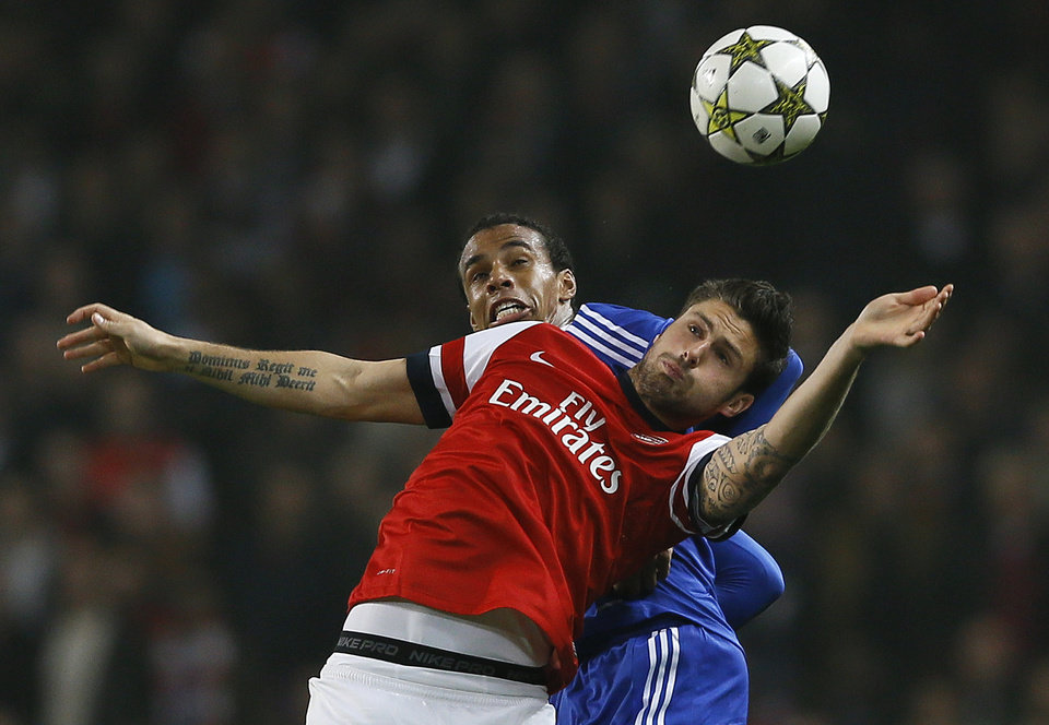 Photo -   Arsenal's Olivier Giroud, front right, heads the ball under pressure from FC Schalke 04's Marco Hoeger during their Champions League group B soccer match between Arsenal and FC Schalke 04 at the Emirates Stadium in London, Wednesday, Oct. 24, 2012. (AP Photo/Kirsty Wigglesworth)