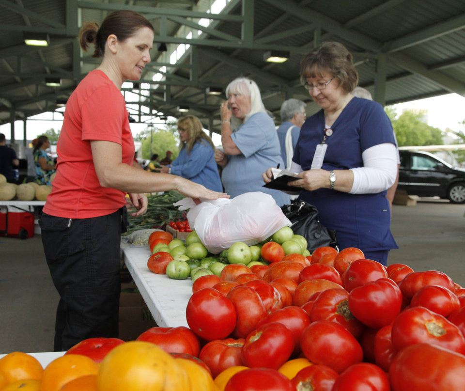 Photo -  Lynne Lusk purchases juicy red tomatoes from Darlene Hathurst, of Hathurst Farms, at the Edmond Farmers Market. PHOTO BY PAUL HELLSTERN, THE OKLAHOMAN   PAUL HELLSTERN -