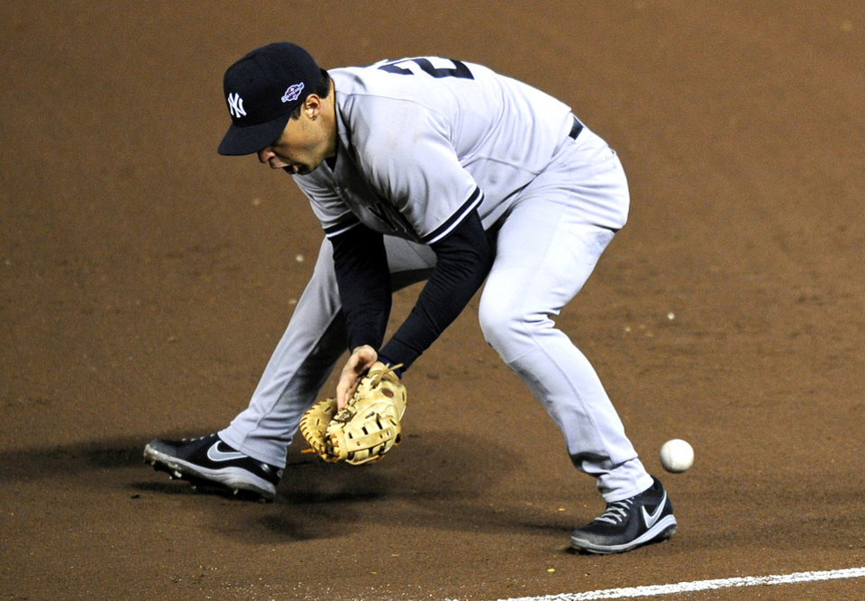 A ground ball that was hit by Baltimore Orioles\' Nate McLouth bounces past New York Yankees first baseman Mark Teixeira in the fifth inning of Game 2 of the American League division baseball series on Monday, Oct. 8, 2012, in Baltimore. McLouth reached first base on Texeira\'s error. (AP Photo/Nick Wass)