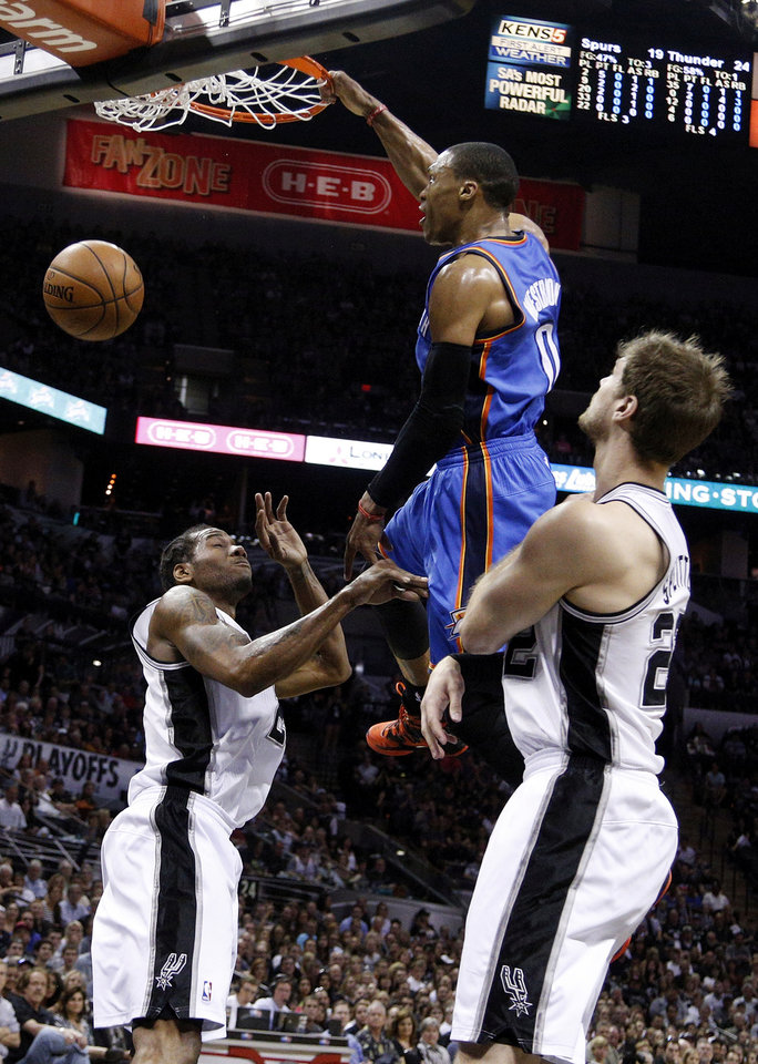 Photo - Oklahoma City's Russell Westbrook (0) dunks the ball between San Antonio's Kawhi Leonard (2) and Tiago Splitter (22) during Game 5 of the Western Conference Finals in the NBA playoffs between the Oklahoma City Thunder and the San Antonio Spurs at the AT&T Center in San Antonio, Thursday, May 29, 2014. Photo by Sarah Phipps, The Oklahoman