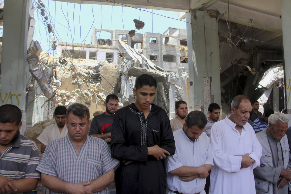 Photo - Palestinians pray the Friday prayer inside a destroyed Al Farouk mosque which was destroyed by an overnight Israeli strike on Tuesday, in Rafah in the southern Gaza Strip on Friday, July 25, 2014. The U.N. chief Ban Ki-moon and the U.S. Secretary of State John Kerry made a new attempt Friday to nail down a temporary truce between Israel and Hamas, as Israel's 18-day military operation in the Gaza Strip fueled new unrest in the West Bank, where several Palestinians were killed during protests. (AP Photo/Hatem Ali)