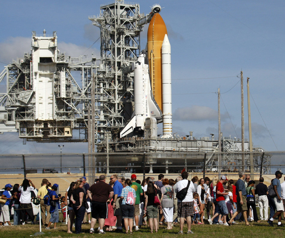 Photo - Tourists view Space Shuttle Discovery after the Rotating Service Structure had moved away from the shuttle during final preparations, Sunday, April 4, 2010, in Cape Canaveral, Fla.  Discovery is scheduled to launch April 5 on a mission to the International Space Station. (AP Photo/Wilfredo Lee)