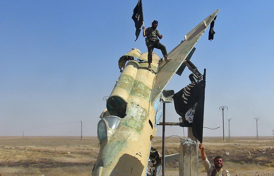 Photo - This undated image posted on Wednesday, Aug. 27, 2014 by the Raqqa Media Center of the Islamic State group, a Syrian opposition group, which has been verified and is consistent with other AP reporting, shows fighters of the Islamic State waving the group's flag from a damaged display of a government fighter jet following the battle for the Tabqa air base, in Raqqa, Syria.   A U.N. commission on Wednesday accused the extremist Islamic State organization of committing crimes against humanity with attacks on civilians, as pictures emerged of the extremists' bloody takeover of a Syrian military air base that added to the international organization's claims.  (AP Photo/ Raqqa Media Center of the Islamic State group)