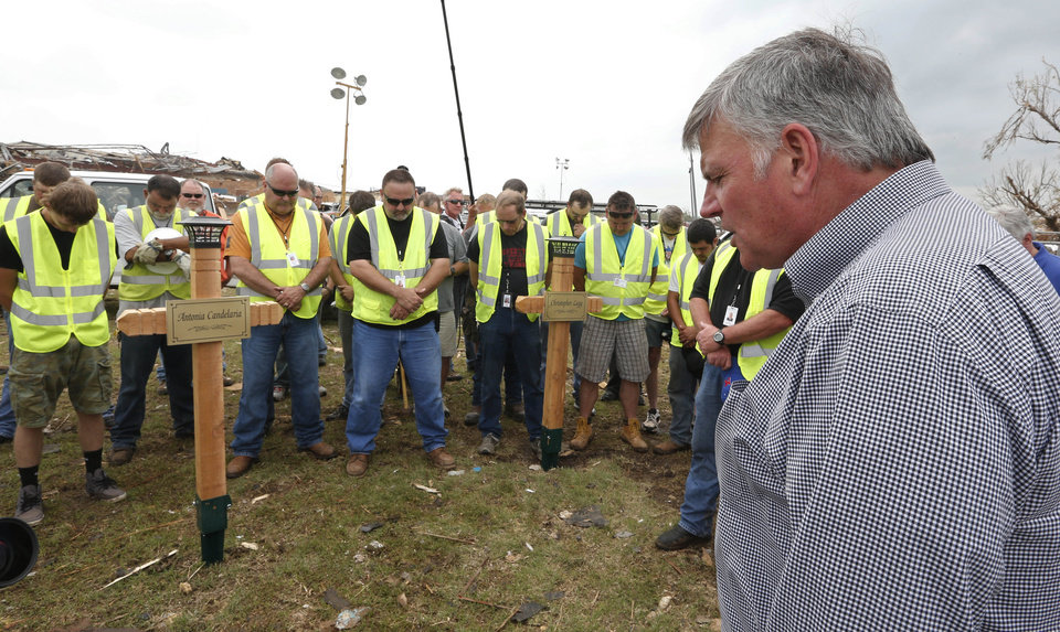 Franklin Graham, right, president of Samaritan\'s Purse, prays with the maintenance workers from the Moore Public Schools who erected crosses at the Plaza Towers elementary school that they built in memory of the seven children who died during the Moore tornado, Friday, May 24, 2013 in Moore, Okla. One large cross and seven smaller crosses with the names of the victims are in memory of the seven students who died in the Moore tornado. (AP Photo/Sue Ogrocki) ORG XMIT: OKSO109