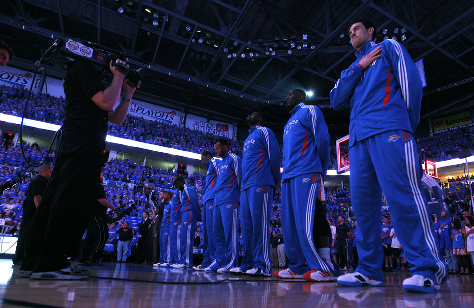 Photo - Nick Collison and the Oklahoma City Thunder salute the flag before the start of the game one of the Western Conference semifinals between the Memphis Grizzlies and the Oklahoma City Thunder in the NBA basketball playoffs at Oklahoma City Arena in Oklahoma City, Sunday, May 1, 2011. Photo by Chris Landsberger, The Oklahoman