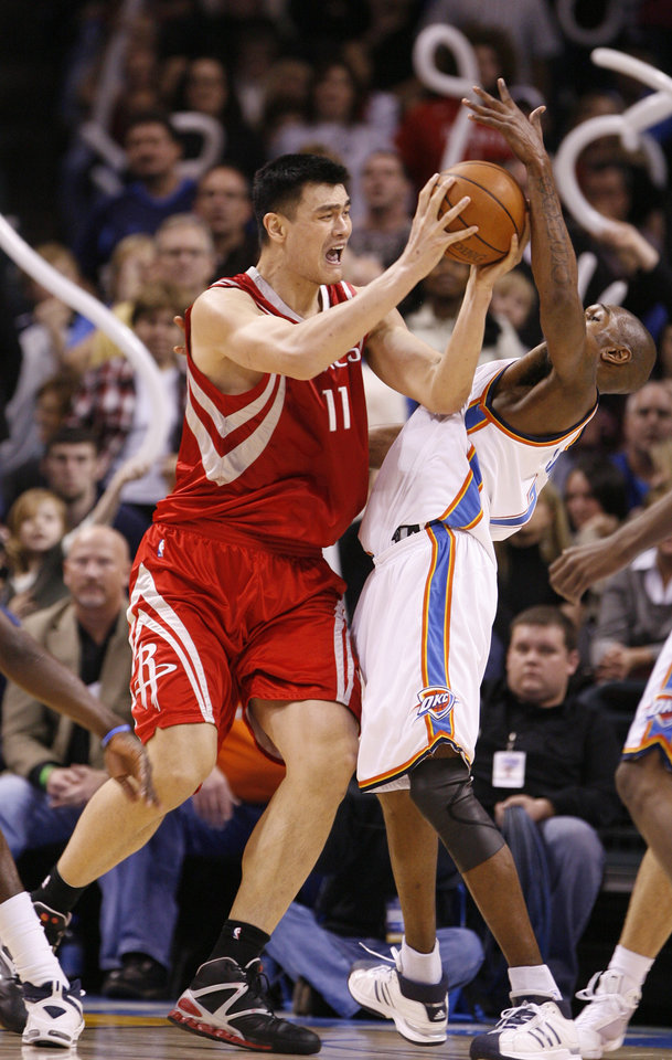 Photo - Yao Ming is called or a charge as he shoots guarded by Joe Smith in the second half as the Oklahoma City Thunder plays the Houston Rockets at the Ford Center in Oklahoma City, Okla. on Friday, January 9, 2009. 