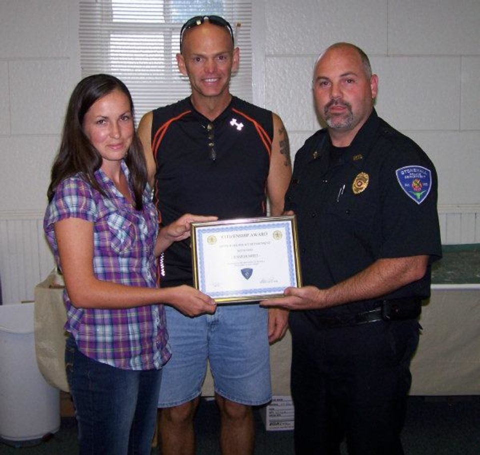 Jennifer Sweet, of Stonewall, accepts the town's first citizen's award for helping Daniel Murray, center, escape a pack of dogs that attacked him on July 8. At right is Stonewall Police Chief Jason Teel. <strong> - PROVIDED BY STONEWALL POLICE DEP</strong>