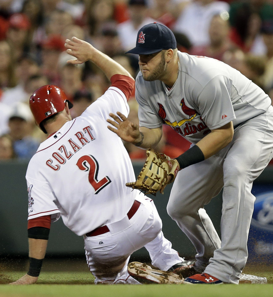 Photo - Cincinnati Reds' Zack Cozart (2) returns safely to first as St. Louis Cardinals first baseman Matt Adams waits for the throw from right field after Mike Leake flew out in the third inning of a baseball game, Sunday, May 25, 2014, in Cincinnati. (AP Photo/Al Behrman)