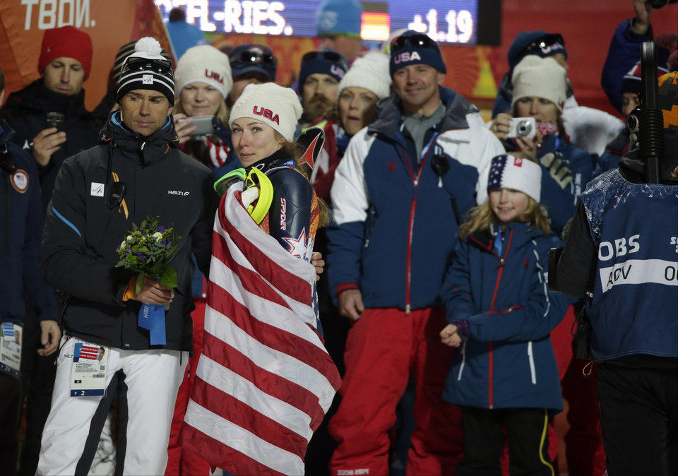 Photo - Women's slalom gold medal winner United States' Mikaela Shiffrin is draped in the American flag after a flower ceremony at the Sochi 2014 Winter Olympics, Friday, Feb. 21, 2014, in Krasnaya Polyana, Russia. (AP Photo/Gero Breloer)