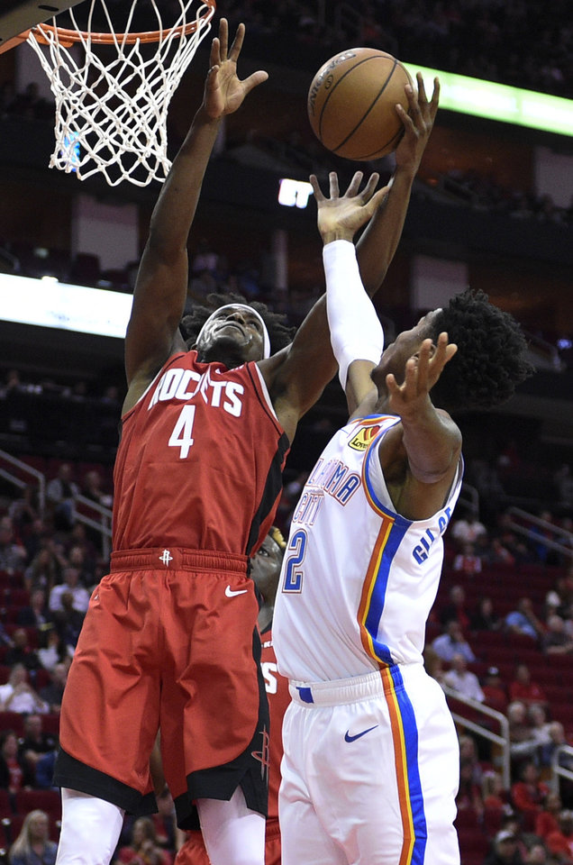 Photo - Houston Rockets forward Danuel House Jr. (4) and Oklahoma City Thunder guard Shai Gilgeous-Alexander vie for a rebound during the first half of an NBA basketball game, Monday, Oct. 28, 2019, in Houston. (AP Photo/Eric Christian Smith)