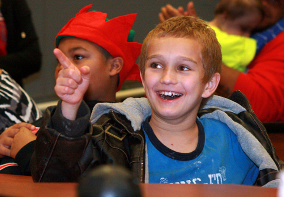 Jesse Jensen, 9, gestures toward the emcee as she announces the winners of a cookie decorating contest at the J.D. McCarty Center's annual Christmas party for children. Jesse took second place for his creation.